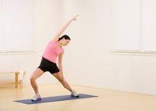 циновка протягивая йогу женщины Стоковые Изображения