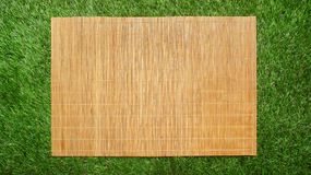 Циновка стиля Азии бамбуковая на предпосылке зеленой травы Стоковое Изображение RF