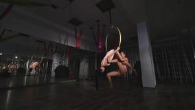 Циркаческие женщины завишут на воздушном обруче акции видеоматериалы