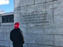 Цитата Nimitz человека читая на стене WWII мемориальной, пока носящ ` делает Америкой большую снова шляпу ` Стоковые Изображения