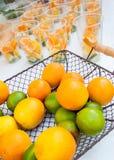 Цитрусовые фрукты в корзине готовой для того чтобы сделать сок с стеклами на заднем плане Стоковое фото RF