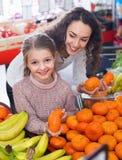 Цитрусовые фрукты матери и малой жизнерадостной дочери покупая Стоковые Изображения