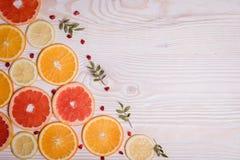 Цитрусовые фрукты отрезали в полу- апельсинах, лимонах, tangerines, грейпфруте на деревянной предпосылке Стоковые Изображения