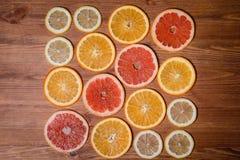 Цитрусовые фрукты отрезали в полу- апельсинах, лимонах, tangerines, грейпфруте на деревянной предпосылке Стоковое Изображение