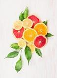 Цитрусовые фрукты составляя с зелеными листьями на белое деревянном Стоковые Изображения