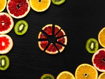 Цитрус и киви обрамляют шаблон на предпосылке texturised чернотой Фото с кусками апельсина, грейпфрута и кивиа в углах Fla плодоо Стоковая Фотография