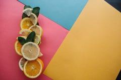 Цитрус на красочной предпосылке Много кусков листьев лимона, апельсина, известки и мяты лежат совместно серия плодоовощей Стоковые Фотографии RF