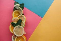 Цитрус на красочной предпосылке Много кусков листьев лимона, апельсина, известки и мяты лежат совместно серия плодоовощей Стоковое Изображение RF