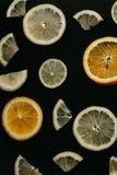 Цитрус на черной предпосылке Много кусков лимона, апельсина и известки лежат совместно серия плодоовощей Витамины и a Стоковое фото RF
