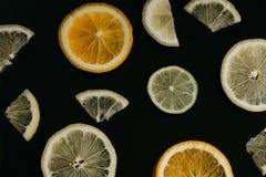 Цитрус на черной предпосылке Много кусков лимона, апельсина и известки лежат совместно серия плодоовощей Витамины и a Стоковое Фото
