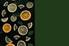 Цитрус на черной предпосылке Много кусков листьев лимона, апельсина, известки и мяты лежат совместно серия плодоовощей витамины Стоковая Фотография