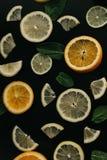 Цитрус на черной предпосылке Много кусков листьев лимона, апельсина, известки и мяты лежат совместно серия плодоовощей витамины Стоковое фото RF