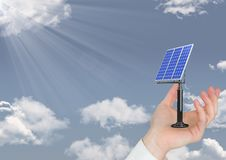 Цифровое изображение руки держа панель солнечных батарей на небе Стоковые Изображения RF