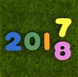 Цифр 2017 до 2018 на зеленой траве стоковая фотография rf
