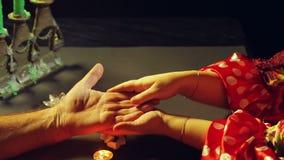 Цыганская женщина в удач-говоря салоне светом горящей свечи интересует человеком рукой видеоматериал