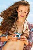 Цыганская молодая женщина стиля на пляже используя ретро камеру фото Стоковые Фотографии RF