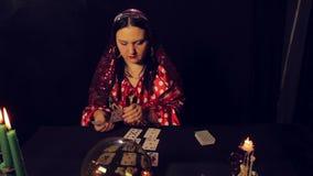 Цыганский рассказчик удачи на таблице светом горящей свечи читает будущее на картах в дыме сток-видео