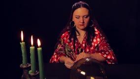Цыганский рассказчик удачи на таблице светом горящей свечи распространяет карты fortunetelling акции видеоматериалы