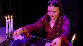 Цыган в красном платье в волшебном салоне светом горящей свечи читает будущее на картах акции видеоматериалы
