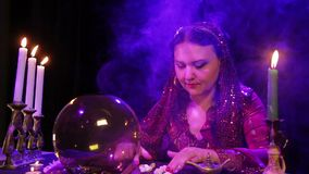 Цыган в красном платье в дыме светом горящей свечи читает будущее камней видеоматериал