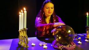 Цыган в красном платье в шарфе читает будущее в шарике зеркала видеоматериал