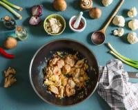 Цыпленок соединяет с специями в сковороде вка на кухонном столе с ингридиентами овощей и деревянной ложкой Стоковое Фото