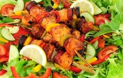 Цыпленок и пряный Chorizo Kebabs с предпосылкой салата Стоковое фото RF