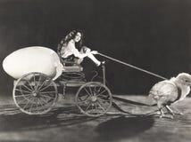 Цыпленок младенца вытягивая тележку с женщиной и гигантским яичком Стоковые Фотографии RF