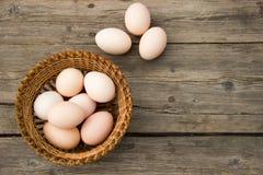 Цыпленок eggs на деревянном столе в взгляд сверху плетеной корзины Стоковая Фотография RF