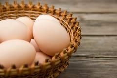 Цыпленок eggs на деревянном столе в плетеной корзине на левой стороне Стоковые Изображения