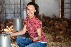 Цыплята жизнерадостного фермера женщины подавая стоковые фото