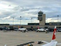 Цюрих-авиапорт ZRH, Швейцария, паркуя швейцарские самолеты в пасмурном сумерк вечера Стоковые Фотографии RF