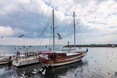 Чайки летают над рыбацкими лодками которые стоят на пристани в Стамбуле, Турции стоковая фотография