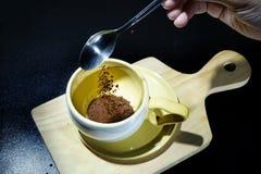 Чайная ложка кофе полита в чашку над разделочной доской Стоковые Фотографии RF