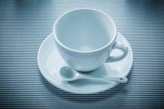 Чайная ложка поддонника кофейной чашки на striped предпосылке Стоковые Изображения RF