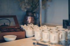 Чайники и чашки пакетиков чая в ресторане на таблице Стоковые Изображения