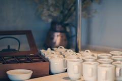 Чайники и чашки пакетиков чая в ресторане на таблице Стоковые Фото