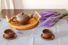 Чайник глины с чашками на таблице, рядом с лавандой стоковые фотографии rf