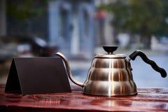 Чайник и черный пустой буклет стоят на деревянном tabl Стоковые Изображения RF