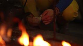 Чайник кипя на пламенах и горящей древесине входит в систему пустыня вечером сток-видео