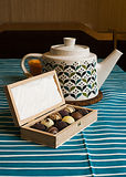 Чайник, свеча и деревянная коробка пралине Стоковая Фотография