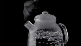 Чайник с кипятком и паром изолированными на черной предпосылке стоковое изображение rf
