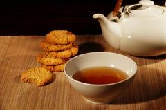 Чайник, чашка чая и печенья в теплом свете Стоковое фото RF