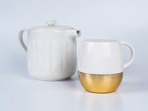 Чайник Infuser с чашкой чая на белой предпосылке стоковое изображение rf