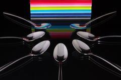 Чайные ложки и 12 дневников на черном стеклянном столе Стоковое фото RF