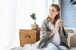 Чай беременной женщины выпивая в кровати Стоковые Изображения