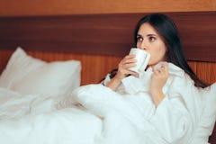 Чай больной женщины выпивая держа бумажные ткани в кровати стоковые фотографии rf