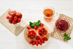 Чай выпивая с tartlets и тортами с клубниками стоковое фото rf