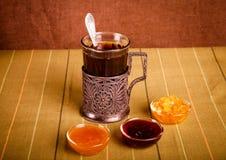 Чай в стекле с держателем, медом и вареньем чашки на зеленой прокладке Стоковые Изображения RF