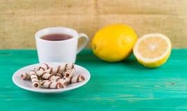 Чай в чашке и tubules вафли в плите Стоковое фото RF